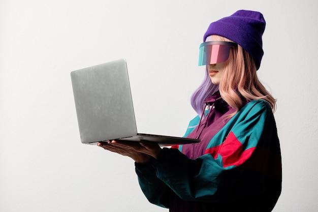 Belle femme à lunettes vr avec ordinateur portable et costume de sport des années 80 sur fond blanc