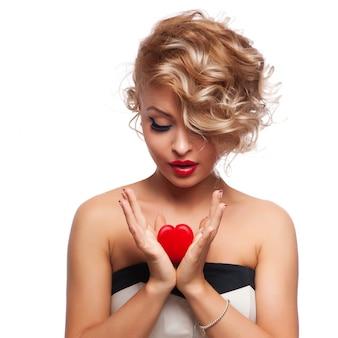 Belle femme magnifique avec un maquillage lumineux glamour et coeur rouge