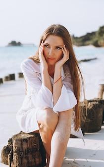 Belle femme en maillot de bain assis au bord de l'océan