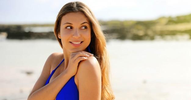Belle femme en maillot de bain bleu sur une plage