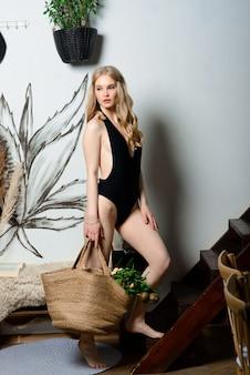 Belle femme en maillot de bain noir avec panier dans un studio