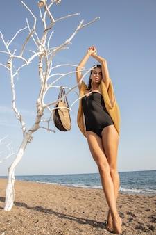 Belle femme en maillot de bain noir sur la plage