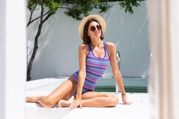 Belle femme en maillot de bain à la piscine de l'arrière-cour à la journée ensoleillée d'été, profitant d'un temps chaud incroyable, attrapant les rayons du soleil