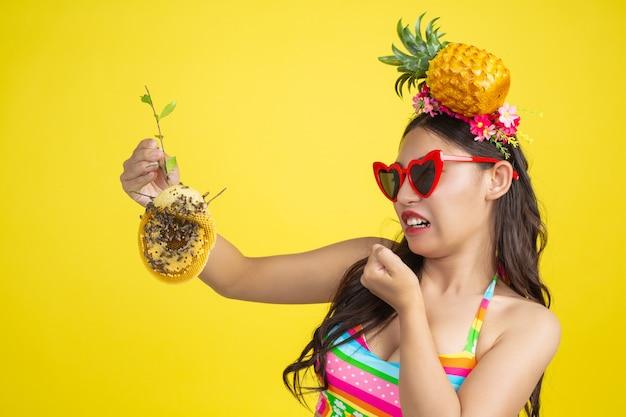 Belle femme en maillot de bain portant un nid d'abeille pose sur jaune