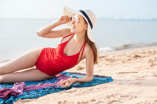 Belle femme en maillot de bain rouge est bronzer sur la plage