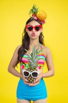 Belle femme en maillot de bain tenant un ananas pose sur jaune