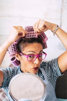 Belle femme à la maison avec des bigoudis sur la tête et un miroir pour voir ce qui se passe - concept amusant de femme moderne en se préparant à se maquiller et à se coiffer