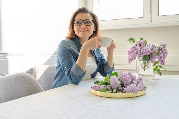 Belle femme à la maison avec bouquet de fleurs lilas