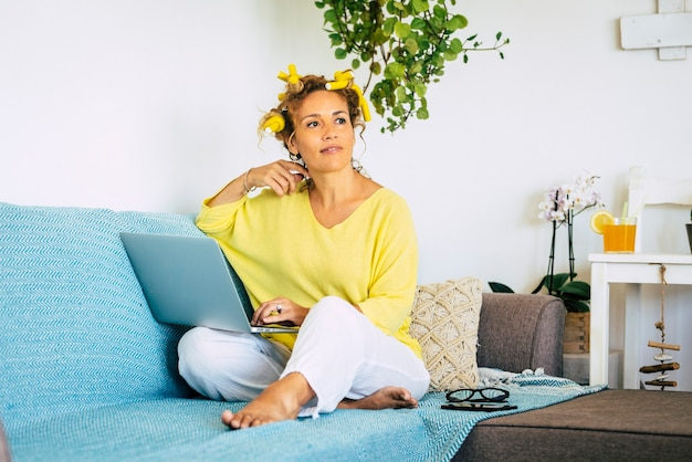 Belle femme à la maison dans une activité de travail intelligente assise sur le canapé et travaillant sur un ordinateur portable