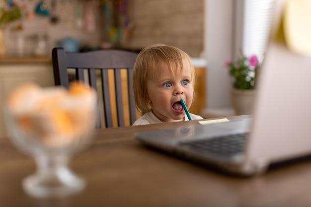 Belle femme à la maison dans la cuisine utilise un ordinateur portable et fait des achats en ligne avec une carte de crédit sur internet