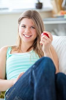 Belle femme mange une pomme à la maison