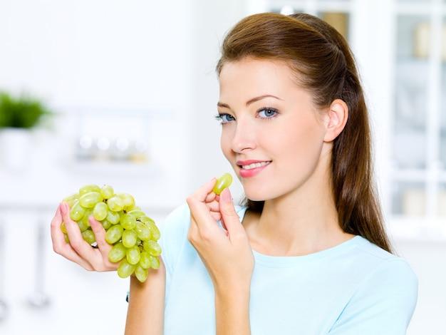 Belle femme mangeant des raisins est dans la cuisine