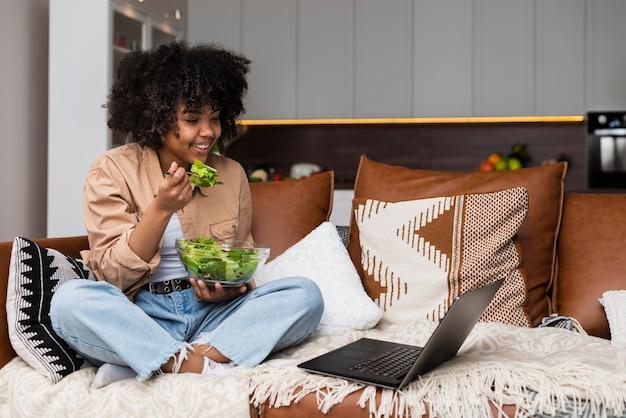 Belle femme mangeant de la salade sur un canapé