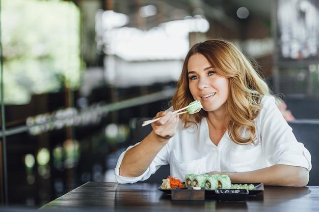 Belle femme, manger, sushi