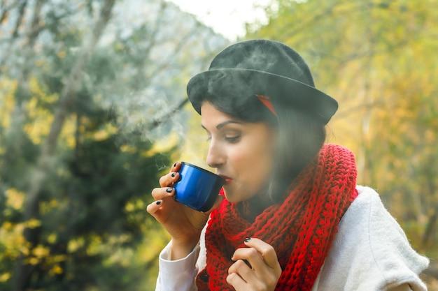 Belle femme en manteau blanc au crochet écharpe rouge et chapeau noir tient une tasse de thé dans ses mains