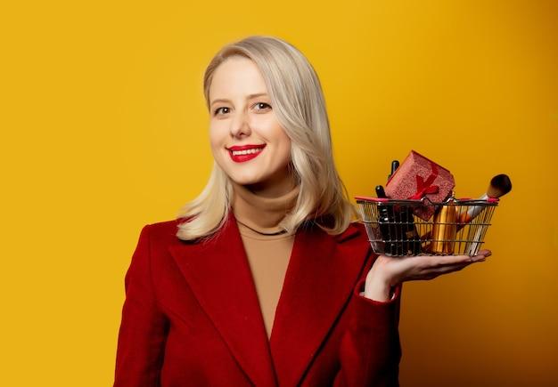 Belle femme en manteau rouge avec panier plein de produits cosmétiques sur mur jaune