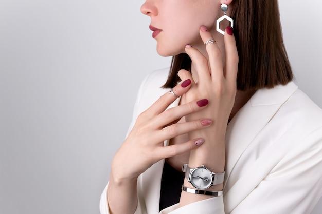Belle femme avec une manucure rose dans un style minimal avec des bijoux