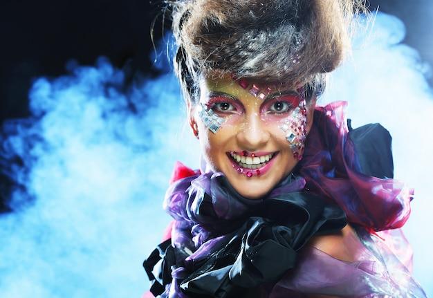 Belle femme avec un maquillage créatif lumineux