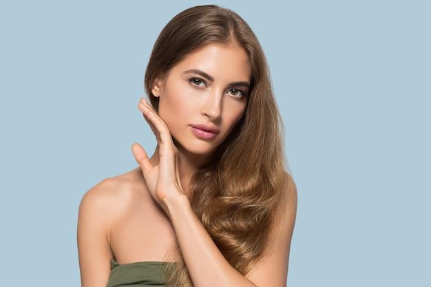 Belle femme avec maquillage naturel cosmétique quotidien décontracté touchant son visage. couleur de fond bleu
