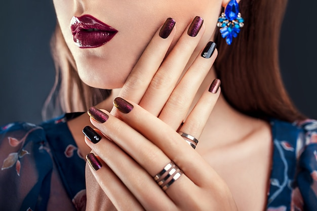 Belle femme avec un maquillage parfait et une manucure portant des bijoux