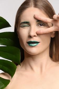 Belle femme avec le maquillage peu commun et la feuille tropicale sur le fond blanc