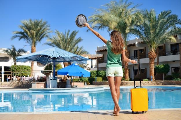 Belle femme marchant près de la piscine de l'hôtel avec valise jaune