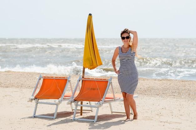 Une belle femme marche au bord de la mer.