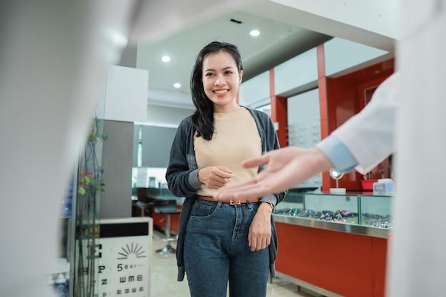 Une belle femme marche lorsque le serveur l'accueille avec un geste de la main à la clinique ophtalmologique