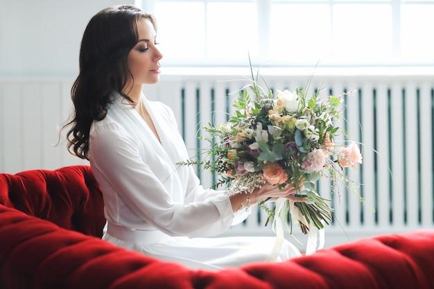 Belle femme mariée en robe de mariée élégante avec bouquet de fleurs