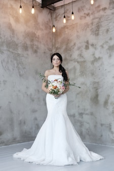 Belle femme mariée en robe de mariée tenant un bouquet de fleurs