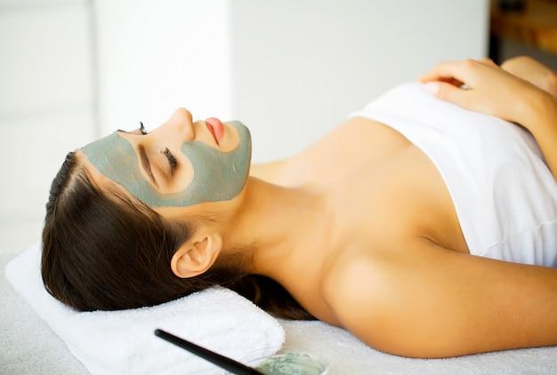Belle femme avec masque cosmétique sur le visage. fille reçoit un traitement dans un salon de spa. masque fait maison pour le visage. traitements de spa.
