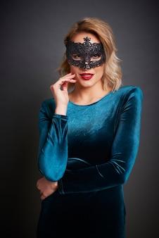 Belle femme avec masque de mascarade en studio tourné
