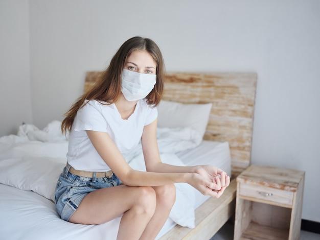 Belle femme en masque médical assise sur le lit en avril isolement pandémie coronavirus