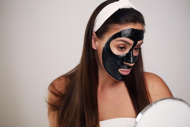 Belle femme avec un masque noir nettoyant sur son visage.