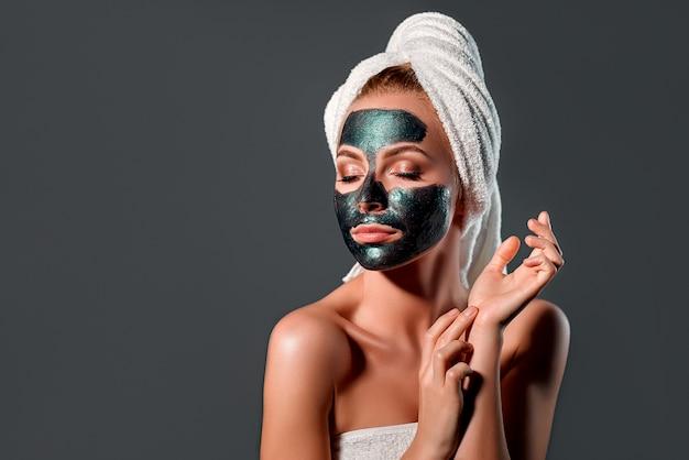 Belle femme avec masque peel-off vert sur un mur gris.