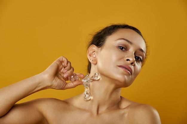 Une belle femme massant le cou avec masseur pharaon isolé sur fond jaune