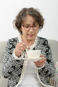 Belle femme mature, boire du thé