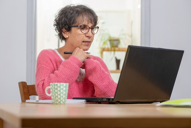 Belle femme mature brune vêtue de rose avec ordinateur portable à la maison