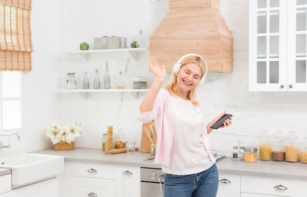 Belle femme mature, écouter de la musique dans la cuisine