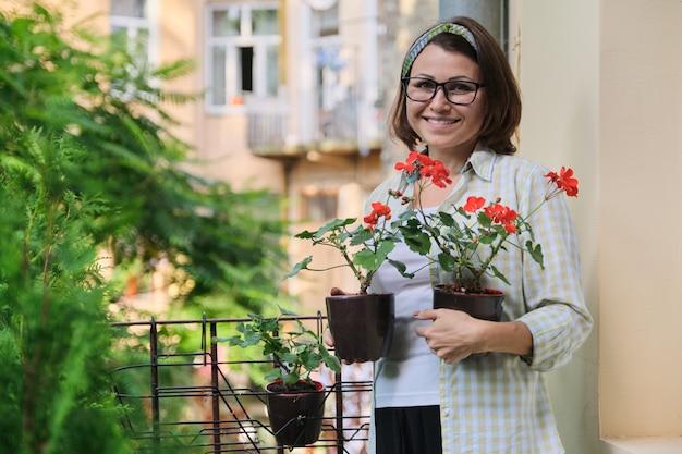 Belle femme mature avec des fleurs d'été rouges en pot souriant au balcon extérieur de la maison, beauté, passe-temps et loisirs d'une femme d'âge moyen, espace pour copie