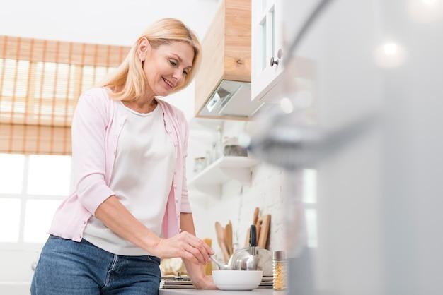 Belle femme mature servant le petit déjeuner à la maison