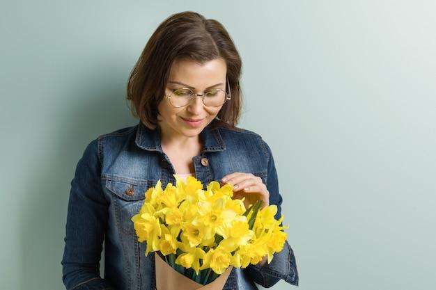 Belle femme mature tenant le bouquet de fleurs de printemps jaune
