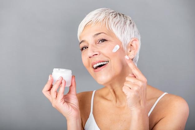 Belle femme mature tenant un pot de crème hydratante et regardant la caméra. heureuse femme senior tenant une bouteille de lotion anti-âge isolée sur fond gris. soin anti-âge et beauté.