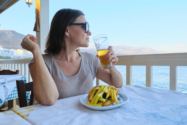 Belle femme mature en train de dîner au café de la station balnéaire. femme mangeant et buvant de la bière légère, savourant un repas avec une boisson et un coucher de soleil pittoresque sur la mer