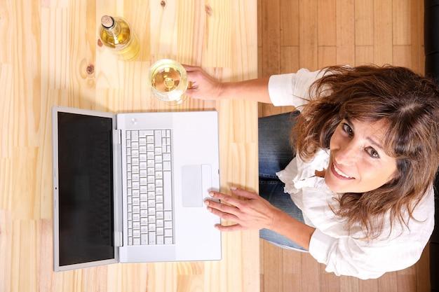 Une belle femme mature avec un verre de vin blanc devant l'ordinateur portable.