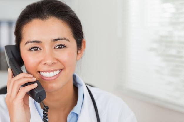 Belle femme médecin au téléphone et posant