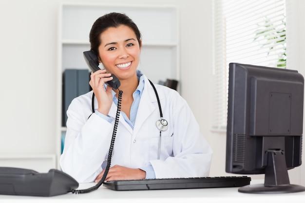 Belle femme médecin au téléphone en position assise
