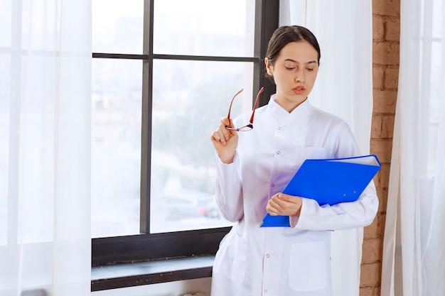 Belle femme médecin en blouse blanche avec dossier debout près de la fenêtre.