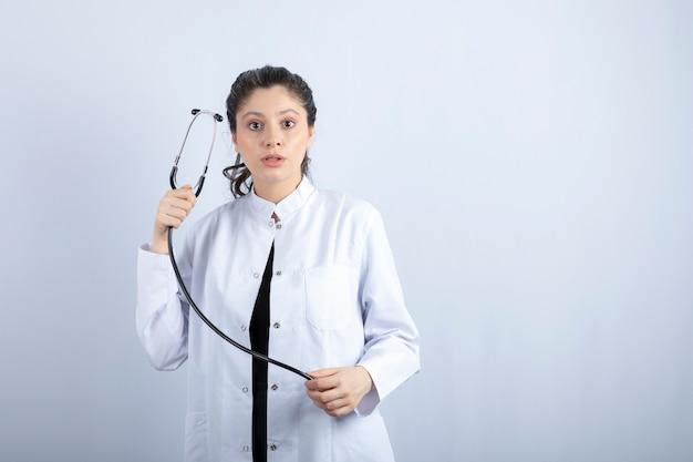 Belle femme médecin en blouse blanche montrant un stéthoscope sur un mur blanc.