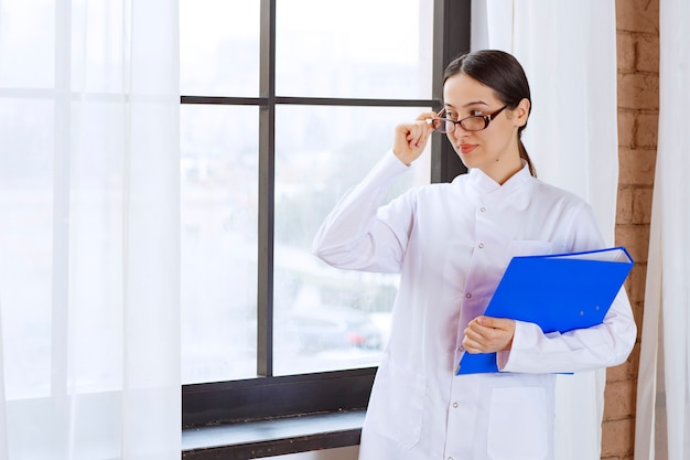 Belle femme médecin à lunettes avec dossier regardant quelque part près de la fenêtre.